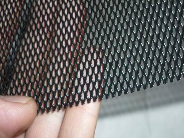 A piece of black powder coated aluminum expanded mesh in a man's hand