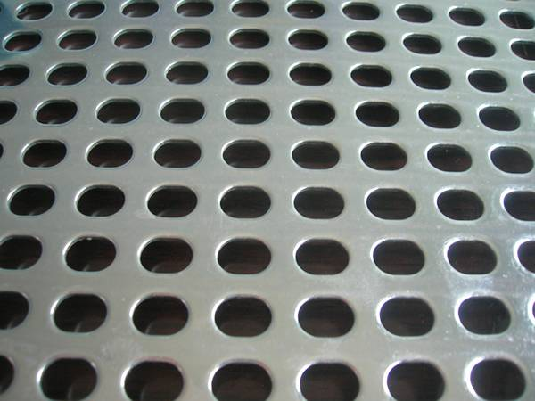 A piece of perforated aluminum metal sheet with oval shape holes in straight rows