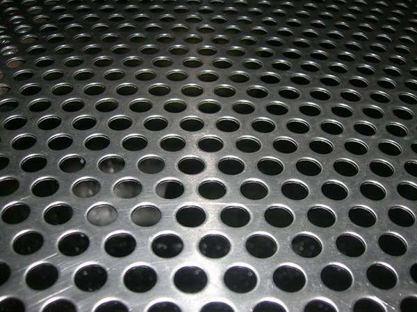 A piece of aluminum perforated metal sheet with round shape holes in staggered row patterns.